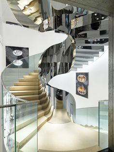 The staircase, with its balustrades of mirror­ polished stainless steel and glass, connects five of the six levels. Photography by Luc Castel.