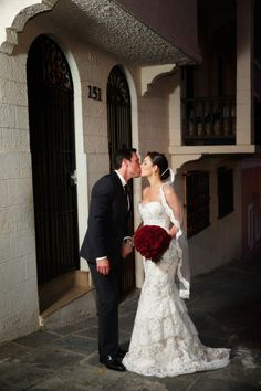Wearing Alvina Valenta style 9161, real bride Carissa and husband Greg kiss on their big day
