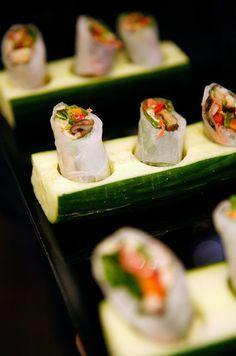 Spring rolls o arrolladitos de verduras servidos sobre pepinos tallados. Una forma creativa para servir las mini foods para bodas creadas por Peter Callahan Catering.