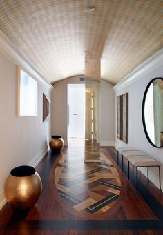"""""""The pattern in the floor creates an anchoring element that's like a built-in carpet in wood,"""" says architect Alexander Gorlin of the entryway to his clients' New York City pied-à-terre. It was the most difficult space to design due to structural restrictions—the central column could not be moved, so Gorlin chose to cover it in antique mirrors. The bronze pots and stools were found on 1stdibs 