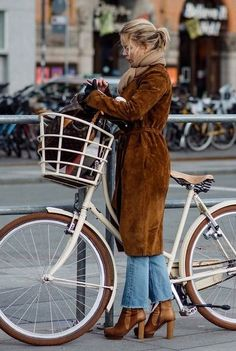 Great Cycle chic look. The suede coats looks great with the boots and a beautiful bike.
