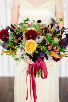 A pretty wild flower fall wedding bouquet adds flirty autumn colors to an all-white wedding.