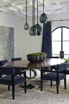 The dining room's chairs, upholstered in a Claremont mohair velvet, are custom made, as is the table by Blackman Cruz; the pendant lights are by David Wiseman, and the painting is by Nick Namarari. - ELLEDecor.com