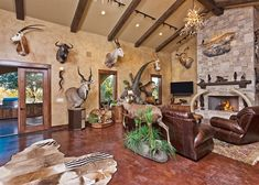 The Trophy Room features stone, timber, glazed walls and stained concrete floors to create the perfect Man Cave environment. Texas Custom Home Builders   Todd Glowka Builder, Inc.