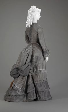 c. 1870   This two-piece visiting dress is made in two shades of gray silk faille. The skirt is lavishly trimmed with pleated silk swags, silk fringe, flounces and piping. Pleated ruching and silk fringe are also used on the bodice. The skirt has a short train and is worn with a bustle. The triangular pocket on the right side of the skirt, trimmed with buttons and cord lacing, was designed to hold a parasol.