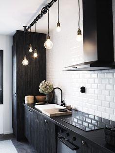 キッチンの頭上に明るいランプが並ります。金属の工業用レールを活用して、ランプのコードを巻いてデコレーション。大きさの異なるランプがかわいらしい。