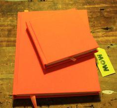 Set MiniMOW + Cuaderno MOW Fluorescente.... Tapa forrada en tela color naranjo fluorescente, 100 hojas papel ahuesado, cinta separadora color naranjo y hojas de guarda color amarillo.