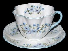 This is a Shelley China, England tea cup and saucer in the Dainty shape and Blue Rock pattern # 13591 with pale blue trim made 1940-1966. The bone china saucer is 5.75 inches in diameter and the cup i