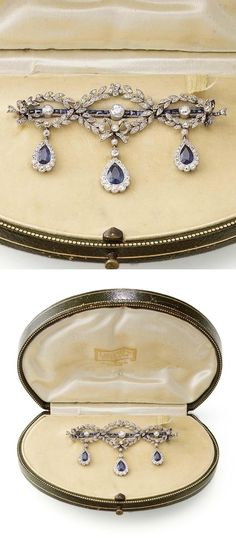 A BELLE EPOQUE SAPPHIRE AND DIAMOND BROOCH, CIRCA 1915. The calibré-cut sapphire and circular-cut diamond bar brooch, decorated with foliate and garland diamond swags, suspending three sapphire and diamond cluster pendants, assay marks to the pin and brooch fitting, vaguely numbered, traces of solder, accompanied by a fitted case by La Cloche Fres, Paris.