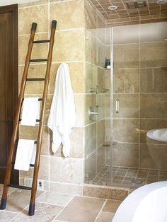 Shower Space -Set between the private toilet compartment and the shower, a ladder functions as a towel rack and also complements the organic environment of this exotic master bath. The ladder is the perfect way to bring in a simple and functional accent piece. Large travertine tiles on the floor and wall create a unified design in this master bath.