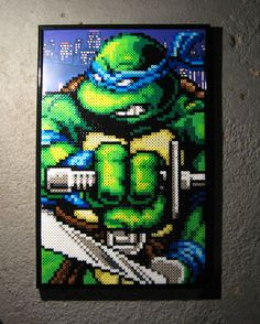 """This piece is an image of Leonardo from the TMNT game The Hyperstone Heist. Leonardo is done with perler beads and is mounted onto a gloss card-stock Photoshop image of the city scene from the opening. Measures 11""""x17""""."""