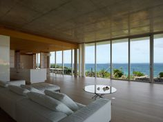 The living spaces and the elevation of this house facing the sea are entirely open and lined with full-height glazing.