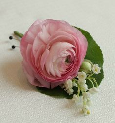 Darling groom, Patrick, wore a simplified duo of ranunculus and lily of the valley with a galax leaf back.