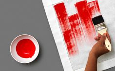 DIY hand painted stripes of red paint directly onto a white napkin