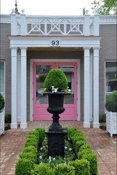 Pink door of Mayme Baker Studio - pink, gray, white, brick and box wood plantings. yes!