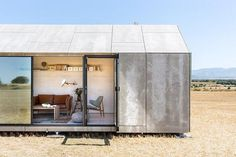 Side view with the panels open of the aph80 Portable Concrete Prefab House by Abaton
