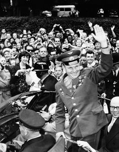 Cosmonaut Yuri Gagarin, stands in an open car outside the Russian embassy in London and waves to the crowd as he departs for home, July 15, 1961
