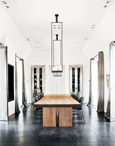 rustic table paired with contemporary black chairs. Looks like a black slate tile floor.