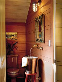 Looking for a compact bathroom sink to fit into a tight space? Try this idea on for size: In the powder room, a metal milk bucket resting on a wooden, three-legged stool was plumbed for use as a sink.  From Southern Living. small spaces, small bathroom, space-saver
