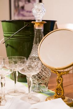 brass vanity mirror, green enamel bucket, gold and cut glass decanter and etched coupe glasses