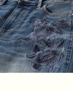 Slightly cropped above the ankles with frayed cuffs, featuring medium washed denim with fading and whiskering, floral embroidery at front, hand-done destruction, a five-pocket styling, nicking and grinding at trims, iconic back pocket stitching and a logo patch.