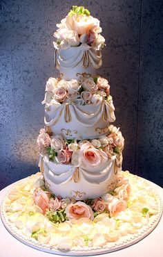 Floral Swag  Tiered cake with fresh flower separation between tiers. Petals around base.