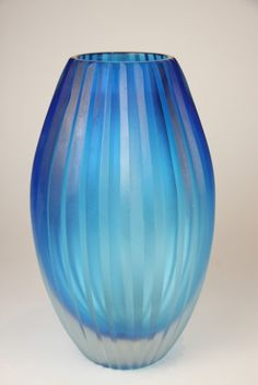 A French Art Deco fluted vase, circa 1920, the ovoid shaped blue glass body set with deep reeded sides. Height 25.5 cm.