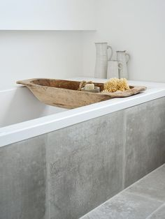 Concrete tiles carry on the bathtub then white penny tiles on wall+ concrete render finish paint on opposite wall