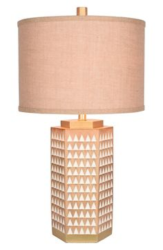 White triangles and golden accents contrast with the faux-wood base of this contemporary table lamp topped with an earthy burlap drum shade.