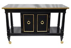 """Stunning server that has been freshly lacquered in black with gilt detailing and hardware. This beautiful piece can be used either as a bar or a buffet. It has two cabinet doors that open to reveal additional storage, and a pull-out silverware drawer. Top surface slides apart, expanding into a bigger serving space measuring 65""""L when fully open. Base is on sliding gilt casters."""