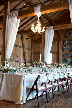 Rustic white themed wedding with chandeliers and white draping.