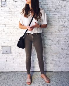 White bodysuit and olive skinnies. White, olive and black outfit. Olive skinny jeans outfit. How to wear olive skinny jeans for spring. Olive for spring. Olive jeans and white top outift. Black saddle bag crossbody. Neutral slide sandals. Nude blush slide sandals