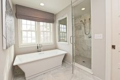 source: Refined LLC    Monochromatic master bathroom with lilac gray walls paint color, purple-ish gray linen roman shade, freestanding modern tub, marble tiles floor and seamless glass shower with marble tiles shower surround.