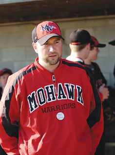 Mohawk baseball coach Eric Hoover watches his team warm up between innings in a recent Midland Athletic League game against St. Wendelin. Ho...