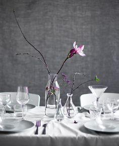 Lag en borddekorasjon med bare kvister og blomster i glassvaser.