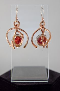18 mm Rusty Red Artist Lampwork beads are featured in a Horseshoe shaped frame. The beads have tones of red, rust, gold, and beige and are wire wrapped onto forged 14 gauge copper wire. An echoing hor