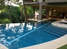 Courtyard home plan in Costa Rica. Wood, five-bedroom, 4.5-bathroom coastal home. Side view of infinity pool.