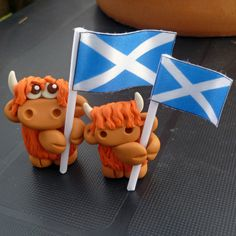 Large Highland Cow with Scotland Flag. Handmade from Sculpey and Fimo polymer clay with a ribbon Saltire.