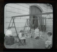 """""""Women and girls reading near swingset where younger children are suspended in hammock like swings, July 1910"""" - Lewis Wickes Hine"""