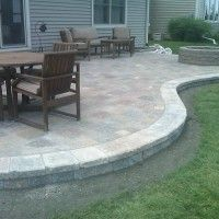 Exterior. Appealing Paver Patio Designs Feature Grey Brick Paver Patio With Circular Fire Pit And Rounded Natural Finished Wooden Table And Natural Finished Wooden Chair With Stripe Fabric Seat Together With Rectangular Natural Finished Wooden Table And Also Natural Finished Wooden Chair With Brown Padded Seat And Glass Sliding Door With White Stained Wood Frame And Also Grey Stained Wooden Wall. Stunning Paver Patio Design Ideas