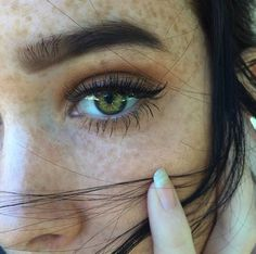 Is this a pretty girl with freckles? Yes. Does she have green eyes? Yes! Brown hair? Yes!! Thank you. Finally.