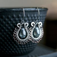 These small oxidized sterling and copper dangle style hoop earrings are adorned with a dainty light blue Czech glass teardrop bead. Earrings