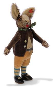 A STEIFF STANDING JACK RABBIT, (28), white and brown tipped mohair, brown and black glass eyes, pink and black stitching, red felt tongue, whiskers, velvet ear linings, swivel head, integral purple velvet jacket, cream shirt, orange knickerbockers and white and blue striped socks, jointed arms, leather shoes and belt, brass buttons and FF button with red cloth tag, 1929 --11½in. (29cm.) high (some discolouration, sole of one shoe replaced)