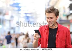 Happy man in red texting on a mobile phone in the street