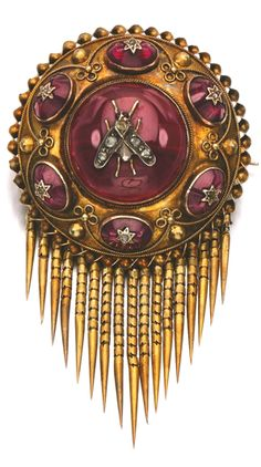 GARNET AND DIAMOND BROOCH, 1870S Designed as a repoussé work disk around a central bee motif, set with cabochon garnets and rose diamonds, suspending an articulated fringe, glass compartment to reverse.