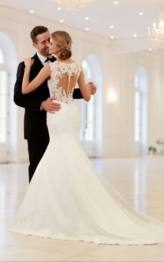 This elegant, sparkling fit-and-flare wedding dress by Stella York is what bridal dreams are made of! Giving this dress a fresh update, the back features illusion lace in a mock keyhole with fabric covered buttons that follow down through to the dramatic satin train. The lace covers the bodice and continues through the hips, giving brides a natural hourglass shape. Mirroring the lace from the bodice, the skirt is trimmed with scalloped lace for a final detail.