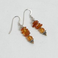 "These handcrafted gemstone amber earrings feature semi-precious, round amber gemstones and chips, fishhook-style earwires, and sterling silver accent beads. 1 3/4"" in length. Add a necklace, pendant a"
