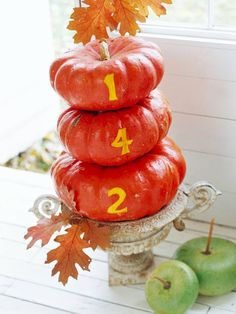Pumpkin Welcome  Greet your guests at the door with a pumpkin house number sign. Stack small, medium, and large Cinderella pumpkins (removing the stems, except for the top one), and trace stenciled number outlines using a crafts knife. Then scrape the pumpkin skin out of the stenciled numbers, revealing the lighter pumpkin flesh underneath.