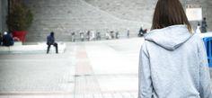Jente i grå hettegenser med ryggen til