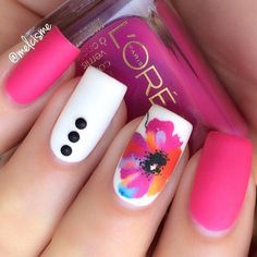 An out of the box pink nail art design. A variety of interesting colors are used for this nail art design with pink and white as the primary base colors. Fun looking designs such as buttons and a flower is also added.